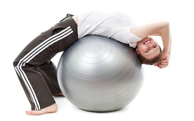 Kobieta ćwicząc na piłce rehabilitacyjnej