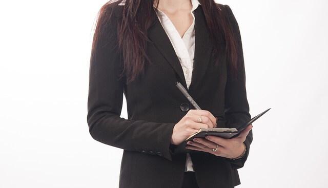 kobieta w marynarce z notesem na rozmowie kwalifikacyjnej