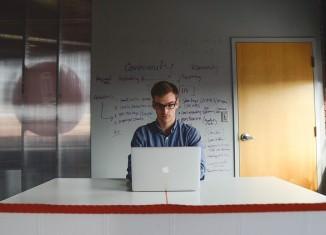 Mężcyzna siedzący przy laptopie w sali