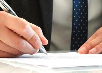 Mężczyzna z graniturze podpisujący papiery