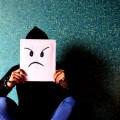 człowiek chowa twarz za kartką z ponurym wyrazem twarzy