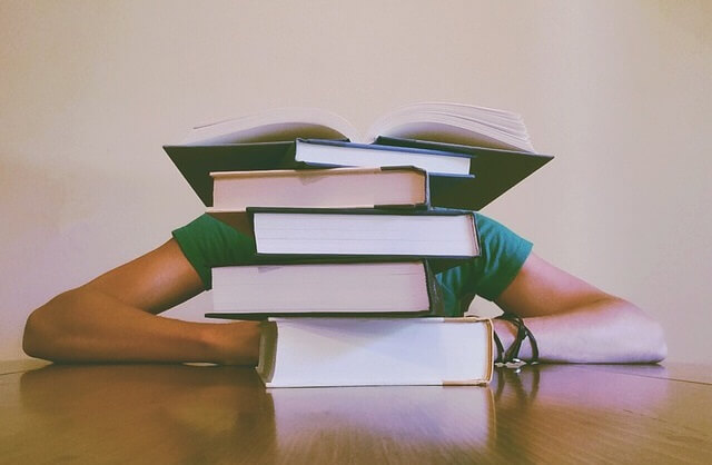 Student chowający się za stertą książek