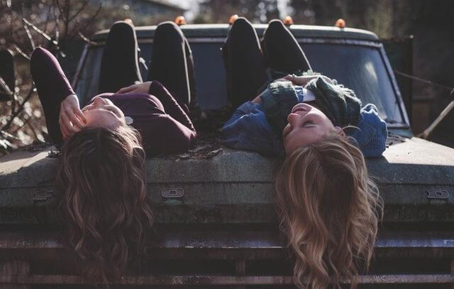 Kobieta i mężczyzna leżący na masce samochodu
