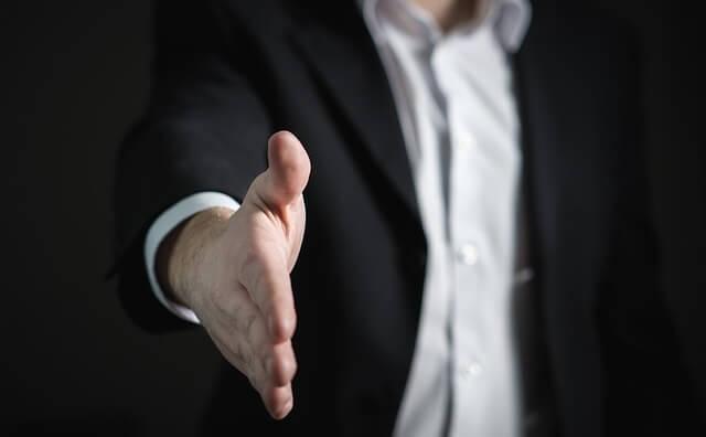 Mężczyzna w garniturze z wyciągniętą dłonią
