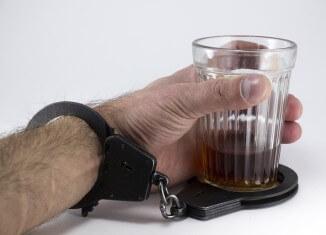 Mężczyzna przykuty kajdankami do szklanki
