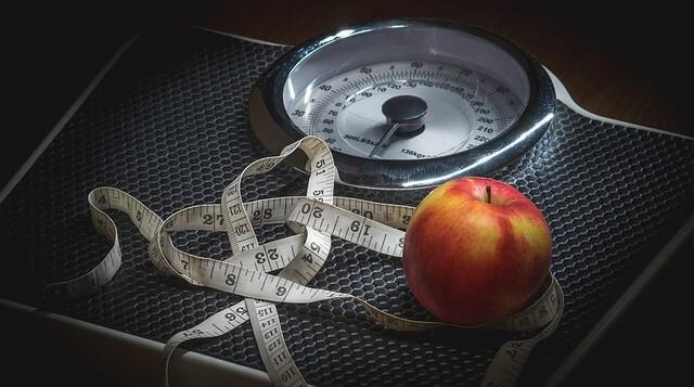 Waga z centymetrem i małym jabłkiem