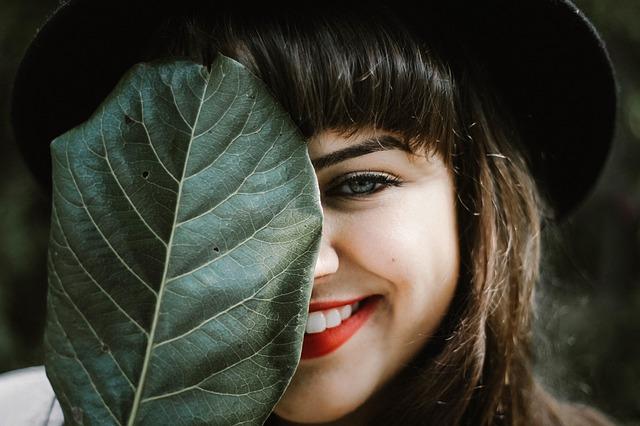 Dziewczyna zasłonięta liściem